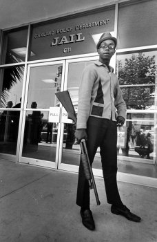 Black Panther Party member Bobby Hutton carries a loaded shotgun in front of the Oakland police